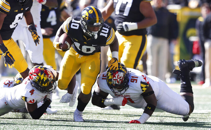 Iowa running back Mekhi Sargent (10) runs between Maryland defenders Darnell Savage Jr., left, and Adam McLean, right, during the first half of an NCAA college football game, Saturday, Oct. 20, 2018, in Iowa City, Iowa. (AP Photo/Charlie Neibergall)