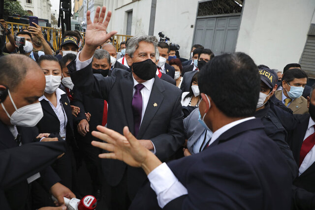 Peru's new interim President Francisco Sagasti waves to the crowd after he was designated by Congress to lead the nation, in Lima, Peru, Monday, Nov. 16, 2020. Congress chose Sagasti to become the nation's third president in the span of a week after Congress ousted Martin Vizcarra and the following protests forced his successor Manuel Merino to resign. (AP Photo/Rodrigo Abd)