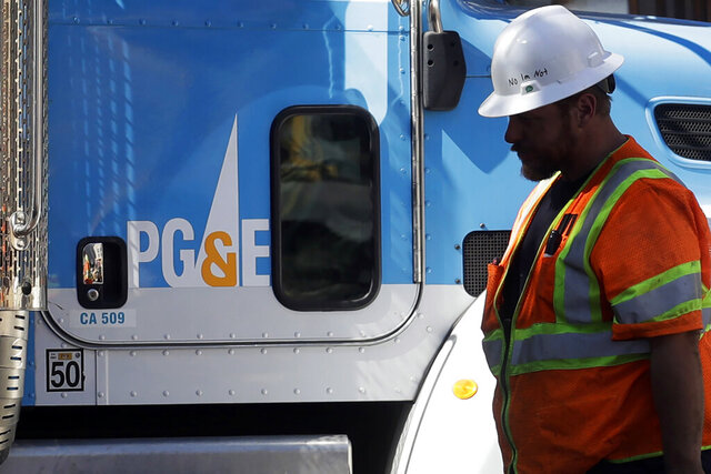 FILE - In this Aug. 15, 2019, file photo, a Pacific Gas & Electric worker walks in front of a truck in San Francisco. Pacific Gas and Electric has reworked a $13.5 billion settlement with victims of deadly wildfires blamed on the utility to try to prevent it from unraveling after California Gov. Gavin Newsom rejected the company's financial rehabilitation plan. The revision discussed in a bankruptcy court hearing Tuesday, Dec. 17, 2019, removes a provision requiring Newsom to approve the deal as a key piece of PG&E's plan to emerge from bankruptcy protection by June 30. (AP Photo/Jeff Chiu, File)