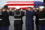 The flag-draped casket of former President George H.W. Bush is carried by a joint services military honor guard Wednesday, Dec. 5, 2018, at Ellington Field in Houston. (AP Photo/David J. Phillip, Pool)