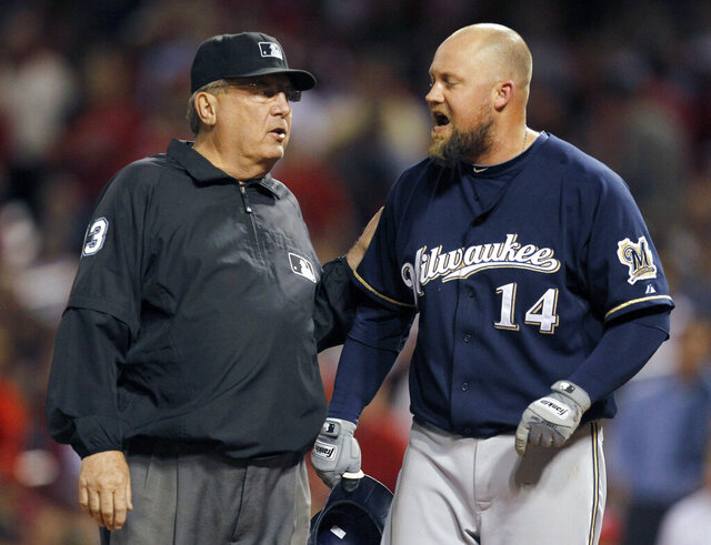 FILE - In this Wednesday, Sept. 7, 2011 file photo, Milwaukee Brewers' Casey McGehee (14) yells at third base umpire and crew chief Derryl Cousins after being thrown out by home plate umpire D.J. Reyburn during the fourth inning of a baseball game against the St. Louis Cardinals in St. Louis. Former major league umpire Derryl Cousins, who worked three World Series during a career that lasted over three decades, has died. He was 74. Craig Cousins said his brother died at home Monday, Oct. 19, 2020 after a bout with cancer. (AP Photo/Jeff Roberson, File)