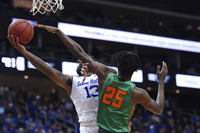 Seton Hall guard Myles Powell (13) attempts a layup as Florida A&M forward DJ Jones (25) defends during the second half of an NCAA college basketball game, Saturday, Nov. 23, 2019, in Newark, N.J. (AP Photo/Sarah Stier)