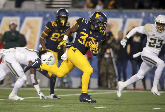 West Virginia running back Martell Pettaway (32) runs for a touchdown during the first half of an NCAA college football game against Baylor, Thursday, Oct. 25, 2018, in Morgantown, W.Va. (AP Photo/Raymond Thompson)