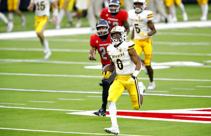 Wyoming running back Xazavian Valladay (6) runs for a 78-yard touchdown run against UNLV during an NCAA college football game in Las Vegas on Friday, Nov. 27, 2020. (Steve Marcus/Las Vegas Sun via AP)