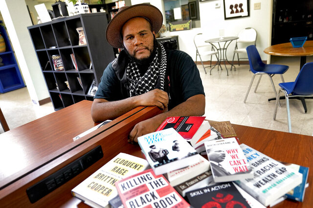 Owner Ali Nervis displays books on race relations at his bookstore Friday, Aug. 21, 2020 in Phoenix. Black-owned bookstores across the U.S. have seen increased sales following the police killings of Breonna Taylor and George Floyd, and store owners are now asking people who have read about Black history and culture to take action against the systems that have enabled racism. (AP Photo/Matt York)
