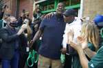 Shawn Kemp, center left, a former NBA basketball player for the Seattle SuperSonics and several other teams, hugs his former teammate and basketball Hall-of-Famer Gary Payton, center right, Friday, Oct. 30, 2020, after Kemp cut the ribbon for Shawn Kemp's Cannabis, the marijuana dispensary he owns with several business partners in downtown Seattle. (AP Photo/Ted S. Warren)