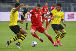 Munich's Robert Lewandowski, center, and Dortmund's Jadon Sancho, right, challenge for the ball during the German Bundesliga soccer match between Borussia Dortmund and FC Bayern Munich in Dortmund, Germany, Tuesday, May 26, 2020. The German Bundesliga is the world's first major soccer league to resume after a two-month suspension because of the coronavirus pandemic. (Federico Gambarini/DPA via AP, Pool)
