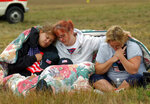 ADVANCE FOR PUBLICATION ON SUNDAY, SEPT. 5, AND THEREAFTER - FILE - In this Wednesday, Sept. 11, 2002 file photo, from left, Shannon Barry, Lisa Starr and Michelle Wagner, all of Hershey, Pa., comfort each other as they listen to a memorial service for victims of Flight 93 near Shanksville, Pa. President Bush will lay a wreath at the crash site later in the day to mark the anniversary of the terrorist attacks. (AP Photo/Julie Jacobson, File)