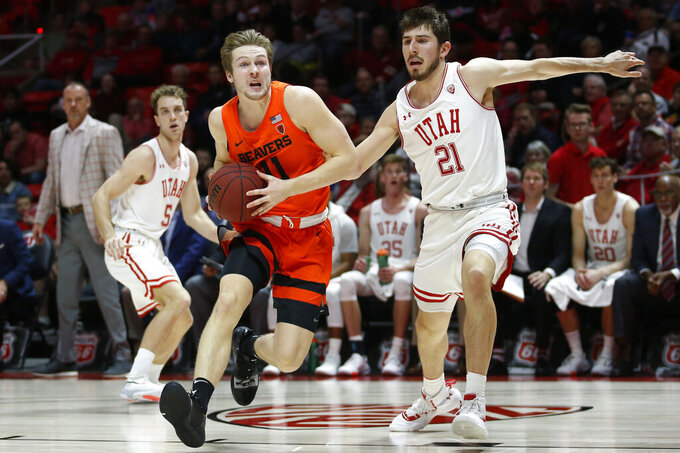 Oregon State guard Zach Reichle (11) drives to the basket as Utah forward Riley Battin (21) defends in the first half during an NCAA college basketball game Thursday, Jan. 2, 2020, in Salt Lake City. (AP Photo/Rick Bowmer)