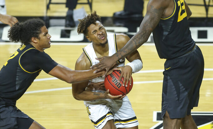 Wichita State guard Tyson Etienne, center, is fouled by Missouri's Dru Smith, left, during the second half of an NCAA college basketball game Sunday, Dec. 6, 2020, in Wichita, Kan. (Travis Heying/The Wichita Eagle via AP)