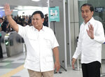 Indonesian President Joko Widodo, right, and his defeated election rival Prabowo Subianto wave at reporters during their meeting at a subway station in Jakarta, Indonesia, Saturday, July 13, 2019. Widodo and the former special forces general met for the first time since the divisive April poll, signaling a calming of political tensions in the world's third-largest democracy. (AP Photo/Dita Alangkara)