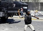A police officer throws a stone at protesters during a protest to demand the resignation of Haiti's president Jovenel Moise in Port-au-Prince, Haiti, Wednesday, Jan. 20, 2021. Moise has one more year in power, but a growing groundswell of opposition is organizing protests and demanding he resign next month amid spiraling crime and a crumbling economy. ( AP Photo/ Dieu Nalio Chery)