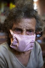 An elderly woman, wearing a make-do protective face mask as a precaution against the spread of the new coronavirus, waits to receive a free meal at a church in The Cemetery neighborhood of Caracas, Venezuela, Friday, May 22, 2020. The number of people who come looking for food at the church has increased during the government ordered quarantine in response to the COVID-19 pandemic. (AP Photo/Ariana Cubillos)