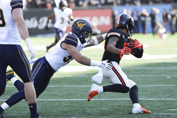Oregon State wide receiver Trevon Bradford slips a tackle from California's Jordan Kunaszyk during the first half of an NCAA college football game in Corvallis, Ore., Saturday, Oct. 20, 2018. (AP Photo/Amanda Loman)