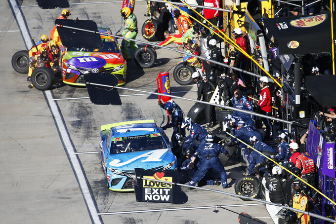 Martin Truex Jr. (19) and Clint Bowyer (14) get service in the pits during the NASCAR Cup Series race at Martinsville Speedway in Martinsville, Va., Sunday, Oct. 27, 2019. (AP Photo/Steve Helber)