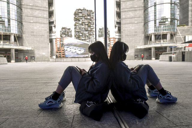A girl wearing a face masks sits checking her phone in downtown Milan's Gae Aulenti square Wednesday, Feb. 26, 2020. The viral outbreak that began in China and has infected more than 80,000 people globally, so far caused 374 cases and 12 deaths in Italy, according to the last figures released by civil protection. (Claudio Furlan/LaPresse via AP)