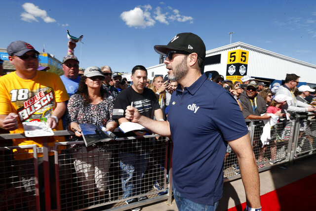 Driver Jimmie Johnson acknowledges fans as he walks to the drivers' meeting prior to a NASCAR Cup Series auto race at Phoenix Raceway, Sunday, March 8, 2020, in Avondale, Ariz. (AP Photo/Ralph Freso)