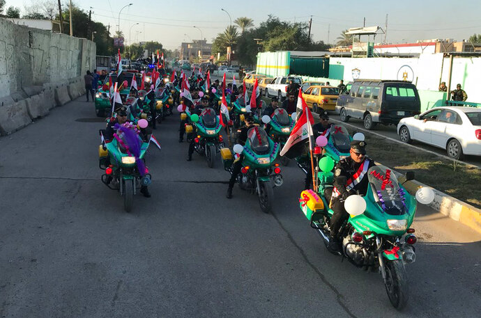 Iraqi security forces parade on motorcycles with national flags marking the year anniversary of the defeat of the Islamic State group in Iraq in Tahrir Square, in central Baghdad, Monday, Dec. 10, 2018. Iraq celebrated the anniversary of its costly victory over the Islamic State group, which has lost virtually all the territory it once held but still carries out sporadic attacks. (AP Photo/Ali Abdul Hassan)