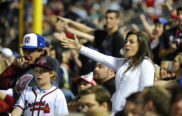 FILE - In this May 2, 2014, file photo, Atlanta Braves fans do the tomahawk chop during the ninth inning of a baseball game with the San Francisco Giants, in Atlanta. The Atlanta Braves say they have no plans to follow the lead of the NFL's Washington Redskins and change their team name. The team said in a letter to season ticket holders they are examining the fan experience, including the tomahawk chop chant, and have formed a