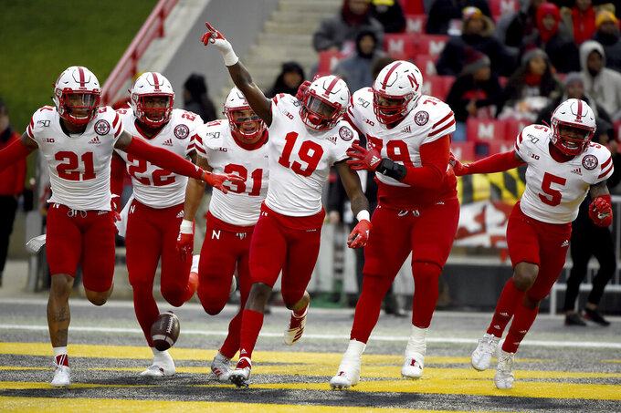 FILE - In this Saturday, Nov. 23, 2019, file photo, Nebraska safety Marquel Dismuke (19) celebrates with teammates after recovering a fumble from Maryland running back Javon Leake (20) during the first half of an NCAA college football game against Maryland, in College Park, Md. Nebraska's 24-sport program has about 600 athletes and is one of a handful that makes money. Though a 10% budget cut was announced recently, the program is able to absorb the cost of coronavirus testing, in part because of its affiliation with the university's medical school.(AP Photo/Will Newton, File)