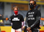 Ferrari driver Sebastian Vettel of Germany, left, and Mercedes driver Lewis Hamilton of Britain, right, stand against racism in the pit lane prior the Styrian Formula One Grand Prix race at the Red Bull Ring racetrack in Spielberg, Austria, Sunday, July 12, 2020. (Mark Thompson/Pool via AP)