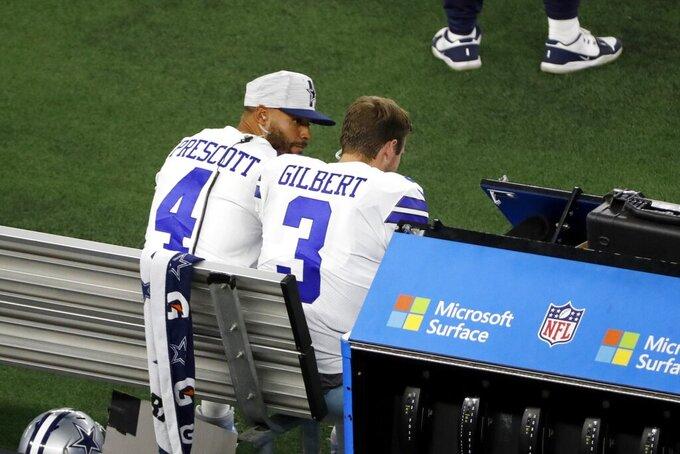 Dallas Cowboys quarterback Dak Prescott (4) and quarterback Garrett Gilbert (3) talk on the sideline in the first half of a preseason NFL football game against the Houston Texans in Arlington, Texas, Saturday, Aug. 21, 2021. (AP Photo/Roger Steinman)