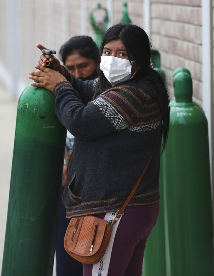 A woman pulls her empty oxygen tank to the line of people waiting outside a shop that refills them in the Villa El Salvador shantytown of Lima, Peru, Thursday, Jan. 21, 2021, amid the COVID-19 pandemic. The store is limited to refilling 20 tanks a day. (AP Photo/Martin Mejia)