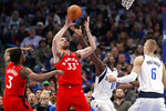 Toronto Raptors center Marc Gasol (33) grabs a rebound over Dallas Mavericks' Dorian Finney-Smith (10) and Kristaps Porzingis (6) and Raptors forward OG Anunoby (3) look on in the first half of an NBA basketball game in Dallas, Saturday, Nov. 16, 2019. (AP Photo/Tony Gutierrez)
