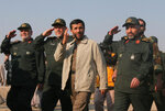 FILE - In this Nov. 26, 2006 file photo, then Iranian President Mahmoud Ahmadinejad, third left, reviews Basij paramilitary volunteers, affiliated to the elite Revolutionary Guard, at a parade ceremony, accompanied by then Basij commander Mohammad Hosseinzadeh Hejazi, right, in front of the mausoleum of the late revolutionary founder Ayatollah Khomeini, in Tehran, Iran. Hejazi, a high-ranking general key to Iran's security apparatus, has died of heart disease, the Islamic Revolutionary Guard Corps announced on Sunday, April 18, 2021. (AP Photo/Vahid Salemi, File)