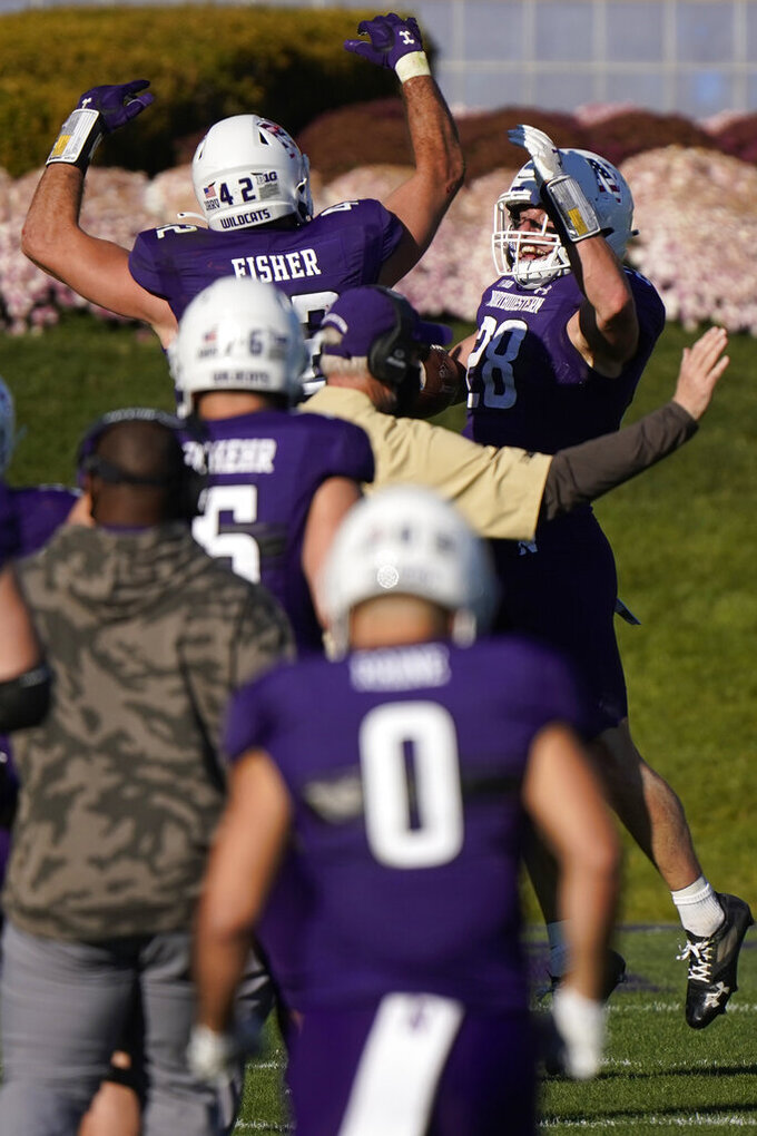 Northwestern linebacker Chris Bergin, top right, celebrates with linebacker Paddy Fisher after Bergin intercepted a pass against Nebraska during the second half of an NCAA college football game in Evanston, Ill., Saturday, Nov. 7, 2020. Northwestern won 21-13. (AP Photo/Nam Y. Huh)