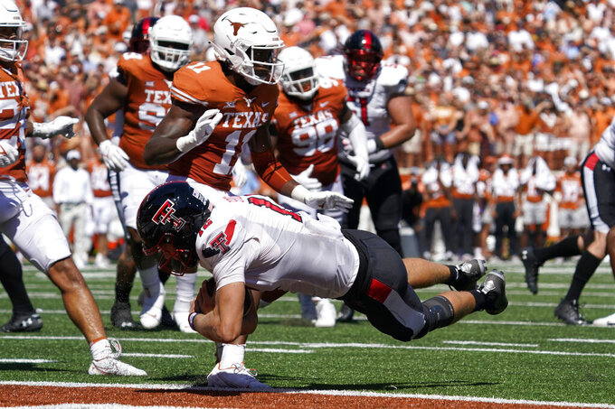 Texas Tech quarterback Tyler Shough (12) dives into the end zone for a touchdown past Texas defensive back Anthony Cook (11) during the first half of an NCAA college football game on Saturday, Sept. 25, 2021, in Austin, Texas. (AP Photo/Chuck Burton)
