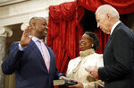 FILE - In this Jan. 3, 2017, file photo, Vice President Joe Biden administers the Senate oath of office to Sen. Tim Scott, R-S.C., as his mother Frances Scott, holds a bible, during a mock swearing in ceremony in the Old Senate Chamber on Capitol Hill in Washington. Initially reluctant to speak on race, Scott is now among the Republican Party's most prominent voices teaching his colleagues what it's like to be a Black man in America. (AP Photo/Alex Brandon, File)