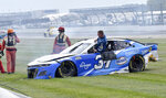 Ryan Preece (37) climbs out of his car after sliding out during a massive crash caused by a piece of curbing during a NASCAR Series auto race at Indianapolis Motor Speedway, Sunday, Aug. 15, 2021, in Indianapolis. (Randy Crist/The Indianapolis Star via AP)