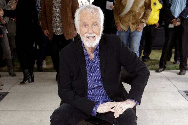 "FILE - In this Oct. 24, 2017 file photo, Kenny Rogers poses with his star on the Music City Walk of Fame in Nashville, Tenn. Actor-singer Kenny Rogers, the smooth, Grammy-winning balladeer who spanned jazz, folk, country and pop with such hits as ""Lucille,"" ""Lady"" and ""Islands in the Stream"" and embraced his persona as ""The Gambler"" on record and on TV died Friday night, March 20, 2020. He was 81. (AP Photo/Mark Humphrey, File)"
