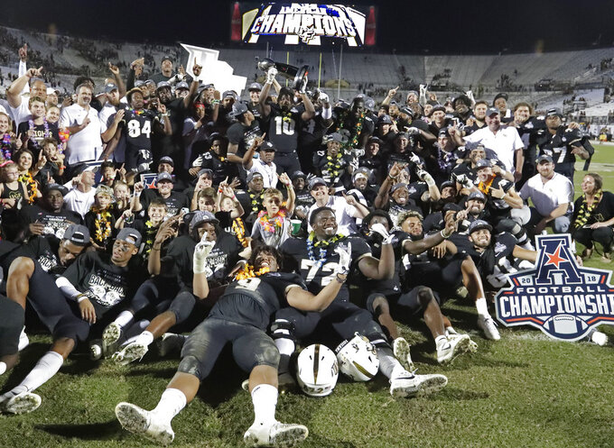 Central Florida players, coaches and family members celebrate after defeating Memphis in the American Athletic Conference championship NCAA college football game, Saturday, Dec. 1, 2018, in Orlando, Fla. (AP Photo/John Raoux)