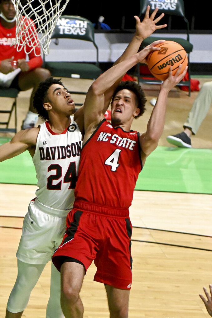 North Carolina State forward Jericole Hellems (4) drives to the basket on Davidson guard Carter Collins (24) in the first half of an NCAA college basketball game in the first round of the NIT, Thursday, March 18, 2021, in Denton, Texas. (AP Photo/Matt Strasen)
