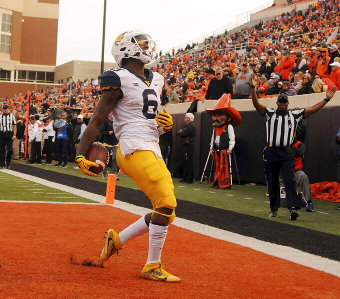West Virginia running back Kennedy McKoy scores a touchdown during the first half of an NCAA college football game in Stillwater, Okla., Saturday, Nov. 17, 2018. McKoy had 2 touchdown in the 41-45 loss to Oklahoma State. (AP Photo/Brody Schmidt)