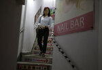 In this photo taken Thursday, Nov. 7, 2019, district council candidate Cathy Yau walks down the stairs of a building during a door-to-door campaign at Causeway Bay in Hong Kong. Yau. a former police officer, grew exasperated as police used more force to quell the unrest. She quit the force in July after 11 years and is running in Sunday's district polls that are widely expected to deliver a decisive victory for the six-month-old movement seeking democratic reforms in the semi-autonomous Chinese territory. (AP Photo/Dita Alangkara)