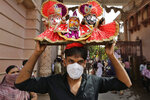 A Hindu devotee wearing a mask carries on his head an idol that depicts Lord Jagannath flanked by sister Subhadra and brother Balram during the annual chariot procession of Lord Jagannath in Ahmedabad, India, Tuesday, June 23, 2020. A symbolic procession was organized in the Lord Jagannath temple premises on Tuesday after the Gujarat High Court rejected the state government's plea to carry out the usual public procession in view of the coronavirus pandemic. (AP Photo/Ajit Solanki)