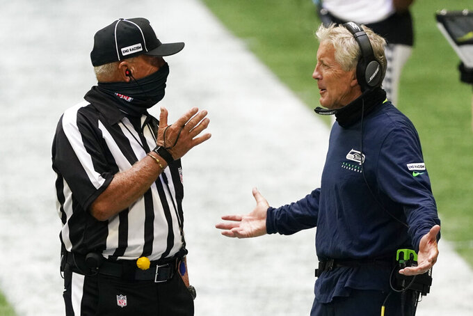 Seattle Seahawks head coach Pete Carroll speaks to an official during the second half of an NFL football game against the Atlanta Falcons, Sunday, Sept. 13, 2020, in Atlanta. (AP Photo/John Bazemore)