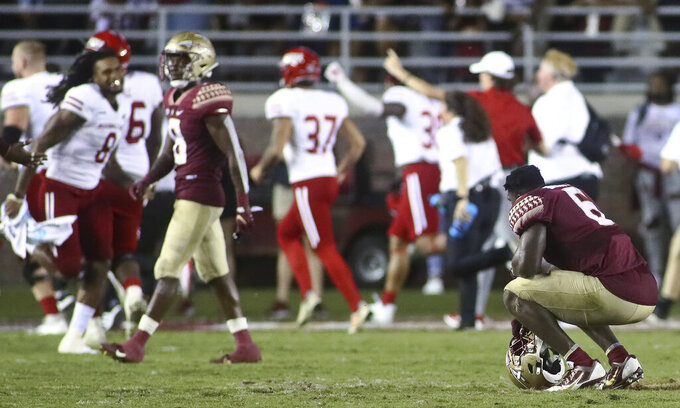 Florida State defensive tackle Dennis Briggs Jr., right, pauses on the field as Jacksonville State celebrates after an NCAA college football game Saturday, Sept. 11, 2021, in Tallahassee, Fla. Jacksonville State won 20-17. (AP Photo/Phil Sears)