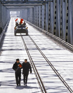 In this photo taken on Feb. 15, 1989, Lt. Gen. Boris Gromov, left, with his son Maxim, walk across a bridge over the Amy Darya River, at Termez, Uzbekistan. When the Soviet Union completed its troops withdrawal from Afghanistan, it was widely hailed as a much-anticipated end to a bloody quagmire, but public perceptions have changed and many Russians now see the 10-year Soviet war in Afghanistan as a necessary and largely successful endeavor. (AP Photo/Vyacheslav Kiselev)