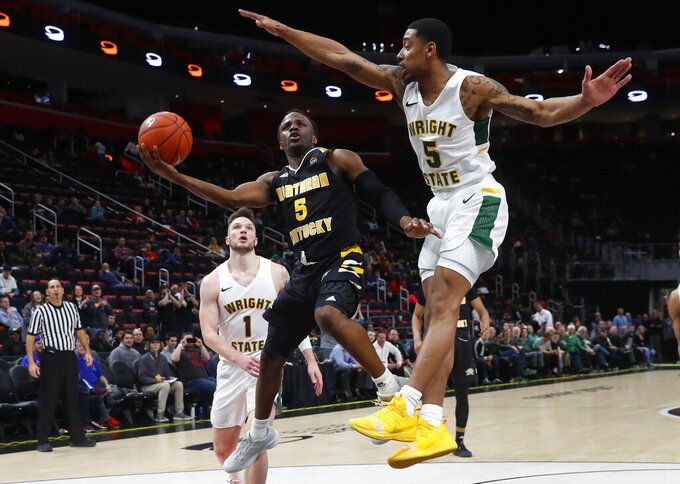 Northern Kentucky guard Zaynah Robinson (5) drives on Wright State guard Skyelar Potter (5) during the second half of an NCAA college basketball game for the Horizon League men's tournament championship in Detroit, Tuesday, March 12, 2019. (AP Photo/Paul Sancya)