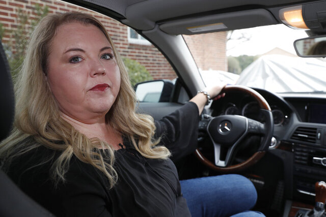 Melinda Slowinski poses for a photo in her 2013 Mercedes E 350 convertible parked in the driveway of her home in Haslett, Texas, Thursday, Feb. 13, 2020. Of all the automakers that are recalling dangerous Takata air bag inflators like the one in Slowinski's car, Mercedes is the laggard when it comes to getting the airbag repairs done. (AP Photo/LM Otero)