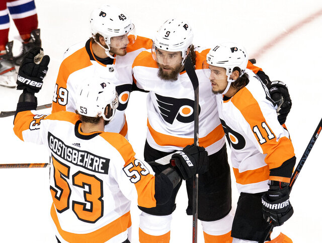 Philadelphia Flyers defenseman Shayne Gostisbehere (53), left wing Joel Farabee (49), defenseman Ivan Provorov (9) and right wing Travis Konecny (11) celebrate after Provorov scored their first goal against the Montreal Canadiens during the first period of an NHL Stanley Cup playoff hockey game in Toronto, Friday, Aug. 21, 2020. (Frank Gunn/The Canadian Press via AP)
