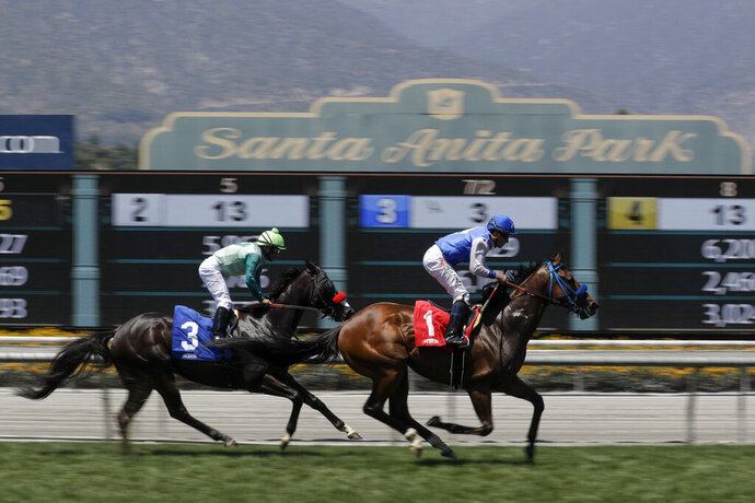 FILE - In this June 23, 2019 file photo Eddie Haskell, right, with jockey Kent Desormeaux aboard, win the third race during the last day of the winter/spring meet at the Santa Anita Park race track in Arcadia, Calif. Governor Gavin Newsom signed a law, Wednesday June 26,2019 that would give the California Horsing Racing Board the authority to immediately suspend the license of Santa Anita. Thirty horses have died at the track in recent months. (AP Photo/Chris Carlson, File)
