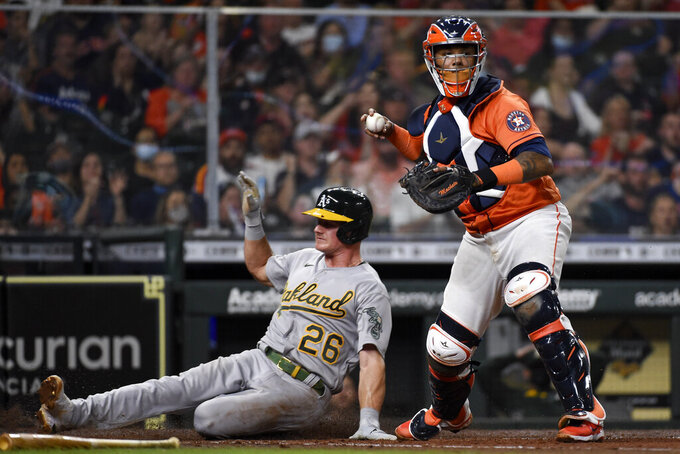 Houston Astros catcher Martin Maldonado, right, forces out Oakland Athletics' Matt Chapman (26) during the fourth inning of a baseball game, Friday, April 9, 2021, in Houston. Elvis Andrus was safe at first on a fielder's choice. (AP Photo/Eric Christian Smith)