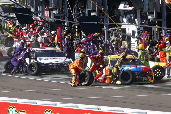 FILE - Kyle Busch, right, and Denny Hamlin make pit stops during the NASCAR Cup Series auto race Sunday, Nov. 10, 2019, in Avondale, Ariz. There is no sport that offers the same access to its stars or the action – teams can and do give spots on their pit stand to honorary guests ranging from friends, family or corporate partners – and it's a critical cog in how NASCAR does business and what draws people to the races.(AP Photo/Ralph Freso, File)