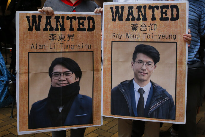 Pro-China protesters hold pictures of Hong Kong activists Ray Wong Toi-yeung, right, and Alan Li Tung-sing during a demonstration near the German Consulate General Consulate in Hong Kong to against Germany in granting a refugee status for the Hong Kong activists, Thursday, May 23, 2019. Germany has granted asylum to two Hong Kong activists in a sign of growing concern over how dissent is dealt with in the territory. (AP Photo/Kin Cheung)
