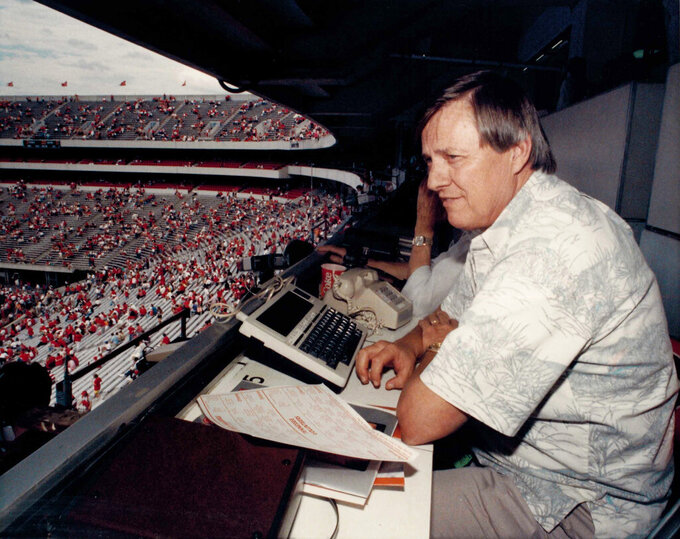 "In this circa 1988 photo, AP sports writer Ed Shearer covers an NCAA college football game between Georgia and Tennessee at Sanford Stadium in Athens, Ga. Shearer, a longtime sports writer with The Associated Press who covered the Olympics, Super Bowl, World Series and Hank Aaron's 715th homer but left his most lasting mark as the ""SEC Seer,"" a prognosticator of Southern football known throughout the nation, died Monday., June 14, 2019. He was 82. (AP Corporate Archives via AP)"
